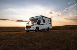 laika camper met laika onderdelen rijdt in natuur met ondergaande zon